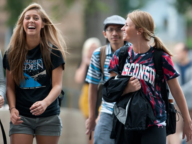 Students laughing while walking across campus