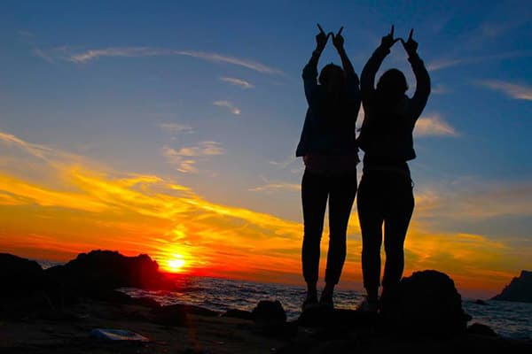 Two study abroad students making the W with their hands on a rocky beach