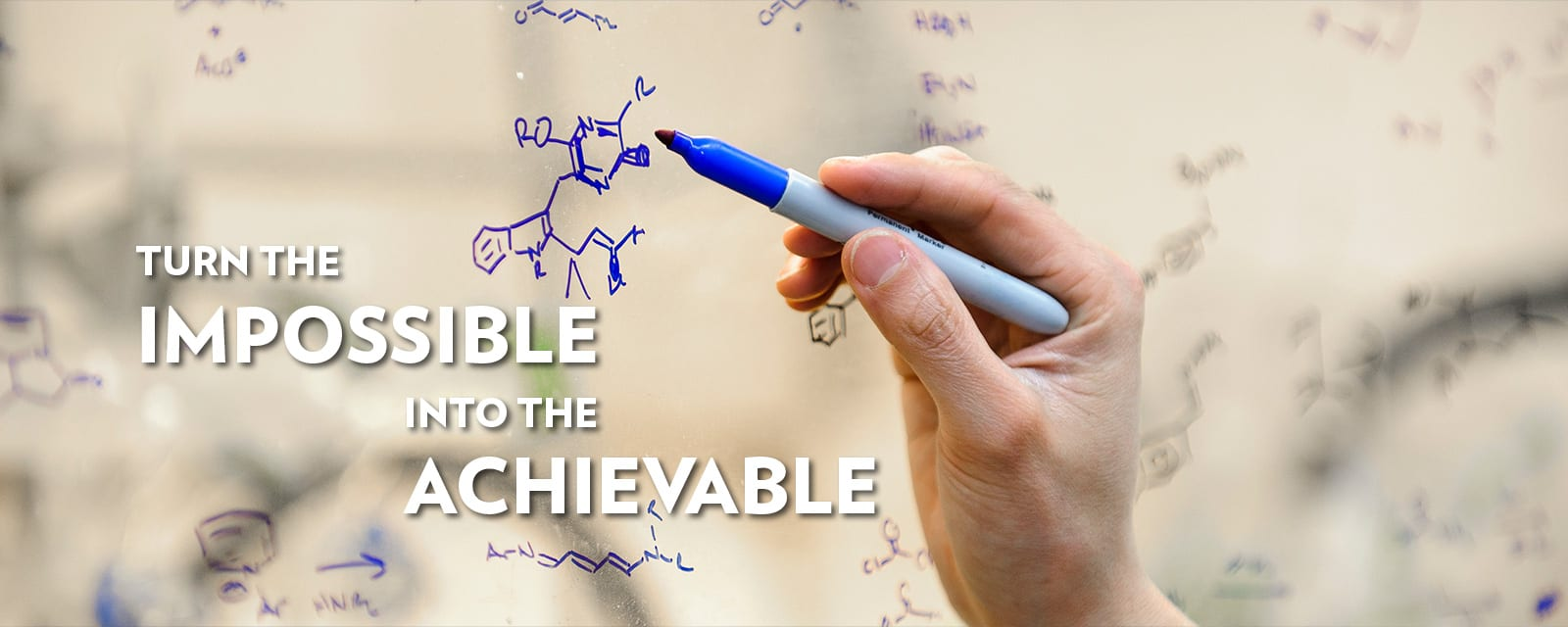 A hand drawing a molecular structure on whiteboard with the words turn the impossible into the achievable