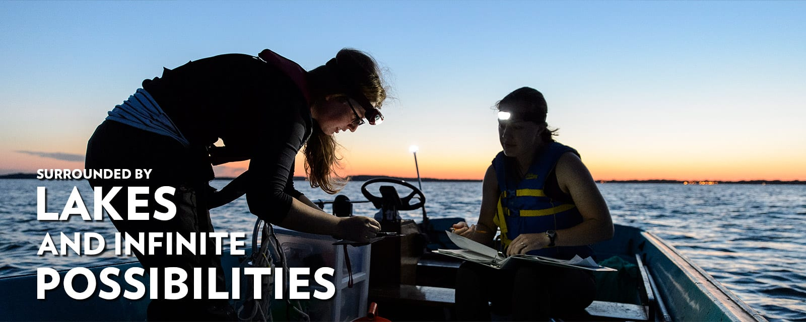 Two students doing research on a small boat at dawn with the words surrounded by lakes and infinite possibilities