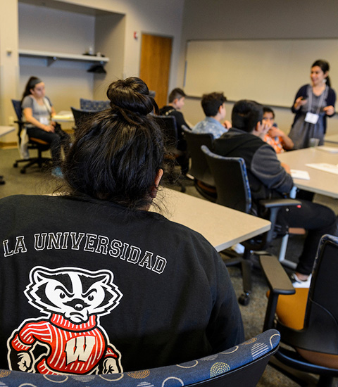 "A Latinx student is seated in a classroom wearing a ""La Universidad"" jacket."