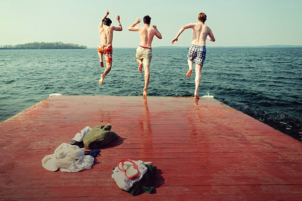 Three students jumping off a pier into Lake Mendota