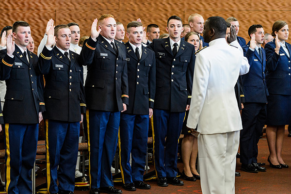 Members of UW–Madison's Army, Navy and Air Force ROTC units stand with their right hand raised in front of a Commander, as they take the oath of office.