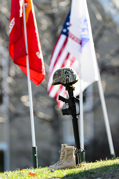 A helmet, rifle and boots on Bascom Hill, with flags in the background.